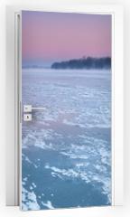 Naklejka na drzwi - Smoking chimneys over a misty and freezing river during dusk
