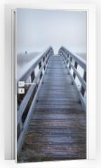 Naklejka na drzwi - wooden bridge via river in winter