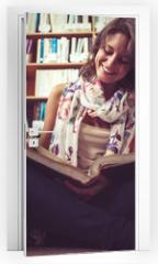 Naklejka na drzwi - Happy female student against bookshelf reading a book on the lib