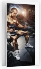 Naklejka na drzwi - Athlete in the gym training with dumbbells