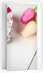 Naklejka na drzwi - High angle shot of pink rosy and yellow Spring tulip flowers and gift box on white wooden table