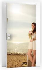 Naklejka na drzwi - Woman standing on beach holding pink tulip
