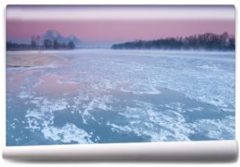 Fototapeta - Smoking chimneys over a misty and freezing river during dusk