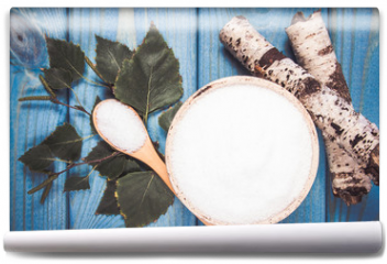 Fototapeta - Xylitol - sugar substitute. Birch sugar on blue wooden background.