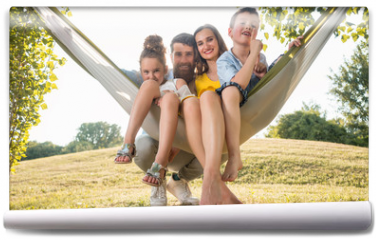 Fototapeta - Family portrait with a beautiful mother of two playful children swinging in a hammock while looking at camera next to her husband outdoors in summer