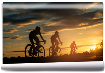 Fototapeta - The men ride  bikes at sunset with orange-blue sky background. Abstract Silhouette background concept.