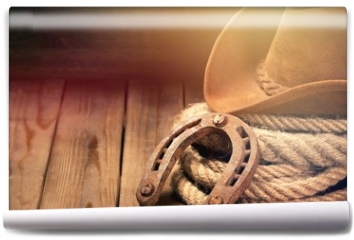 Fototapeta - Old horseshoe , lariat lasso and cowboy hat on background