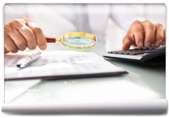 Fototapeta - Businessman Analyzing Financial Report With Magnifying Glass