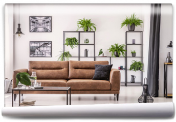 Fototapeta - Table in front of leather sofa in white apartment interior with lamp, posters and plants. Real photo