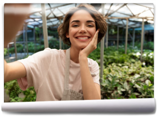 Fototapeta - Gardener standing over plants in greenhouse take a selfie by camera.