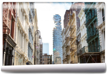 Fototapeta - Sunlight shines on the buildings along Greene Street with a view towards the intersection on Canal Street in SOHO Manhattan, New York City