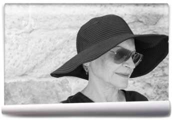 Fototapeta - Head and shoulders view of beautiful older woman in hat and sunglasses against stone wall (black and white)