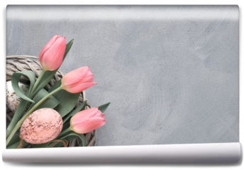 Fototapeta - Springtime or Easter background with pink tulips and Easter eggs in wattle ring on grey concrete, text space