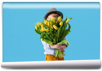 Fototapeta - Cute smiling child holding a beautiful bouquet of yellow tulips in front of his face isolated on blue. Little toddler boy gives a bouquet to mom