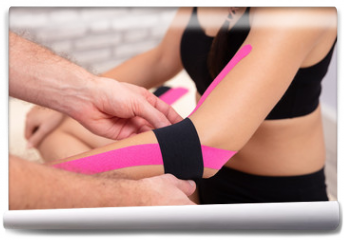 Fototapeta - Man Applying Black Physio Tape On Woman's Hand