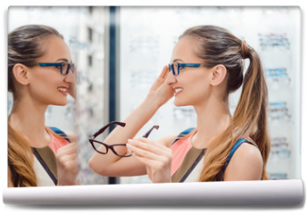Fototapeta - Young woman in optometrists store checking her looks in mirror