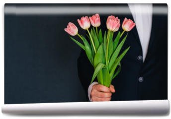 Fototapeta - man's hand giving a bouquet of pink tulips