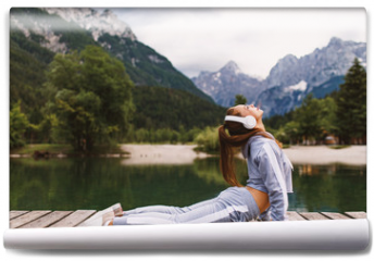 Fototapeta - Young sports woman stretching at dock on the lake in the mountains