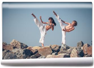 Fototapeta - Children training karate on the stone coast