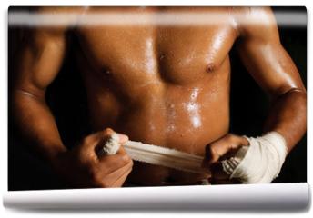 Fototapeta - The muscular fighter tying tape around his hand preparing to