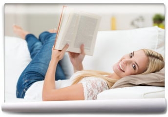 Fototapeta - lächelnde junge frau liest ein buch auf dem sofa