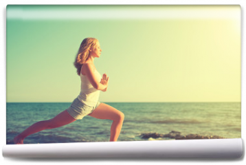 Fototapeta - young woman doing yoga on  beach