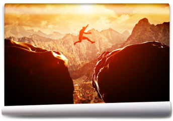 Fototapeta - Man jumping over precipice between two mountains at sunset