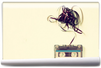 Fototapeta - Cassette tape over wooden table with tangled ribbon. top view. r