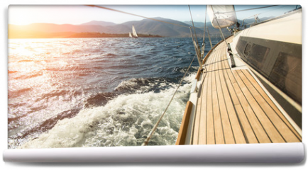 Fototapeta - Yacht sailing towards the sunset. Sailing. Luxury yachts.