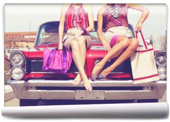 Fototapeta - Beautiful ladies legs posing in a vintage retro car