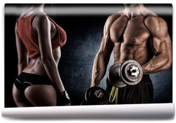 Fototapeta - Closeup of a muscular young man lifting weights