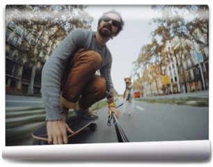 Fototapeta - Man rides his longboard followed by his dog