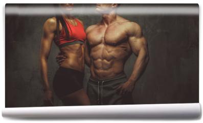 Fototapeta - Woman and man bodybuilders posing in studio