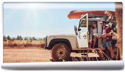 Fototapeta - Młoda para na wycieczce, sprawdzająca mape dojazdu