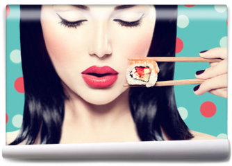 Fototapeta - Beautiful woman holding chopsticks with sushi roll