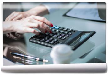 Fototapeta - .closeup.business woman using a calculator at the workplace.
