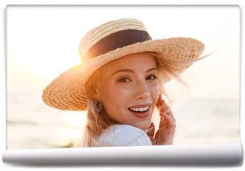 Fototapeta - Cute blonde woman wearing hat outdoors at the beach