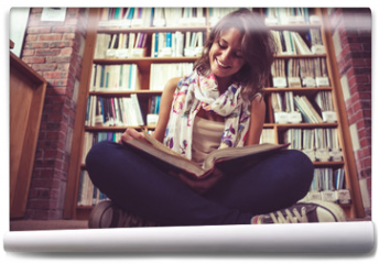 Fototapeta - Happy female student against bookshelf reading a book on the lib