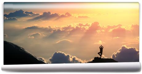 Fototapeta - Practicing yoga outdoors.