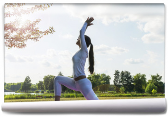 Fototapeta - Pretty woman doing yoga exercises in the park.