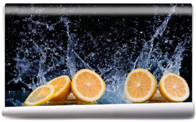 Fototapeta - Sliced lemon in the water on black background