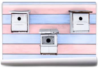 Fototapeta - tres cajas nido blancas sobre fondo de madera rosa y azul