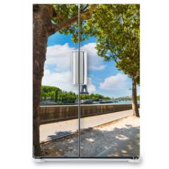 Naklejka na lodówkę - Green trees by Seine River with world famous Eiffel tower on the background