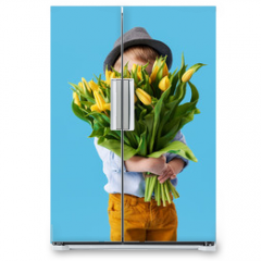 Naklejka na lodówkę - Cute smiling child holding a beautiful bouquet of yellow tulips in front of his face isolated on blue. Little toddler boy gives a bouquet to mom