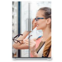 Naklejka na lodówkę - Young woman in optometrists store checking her looks in mirror