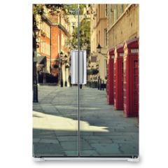 Naklejka na lodówkę - Street with traditional red Phone Boxes, London.