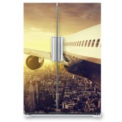 Naklejka na lodówkę - Airplane over a big City