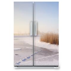 Naklejka na lodówkę - Dutch windmills in a foggy winter landscape in the morning
