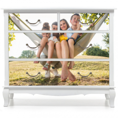 Naklejka na meble - Family portrait with a beautiful mother of two playful children swinging in a hammock while looking at camera next to her husband outdoors in summer