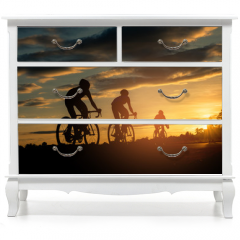 Naklejka na meble - The men ride  bikes at sunset with orange-blue sky background. Abstract Silhouette background concept.